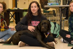 Teen advocate sitting on floor with service dog