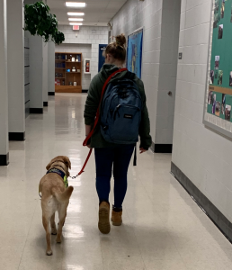 Teen advocate walking through school with service dog